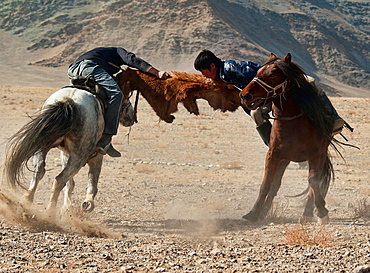 Kazakhs playing kokbar, a traditional sport in which tug of war over a fox or goat pelt is played on horseback, at the Eagle Festival in the Altai Region of Bayan-Olgii in Western Mongolia