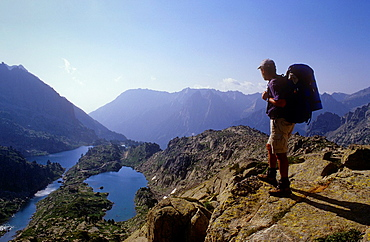 hiker looking 'Estanys de Barbs' and 'Estanys de Munyidera' Barbs and Munyidera lakes, Aiguestortes i Estany de Sant Maurici National Park, Pyrenees, Lleida province, Catalonia, Spain