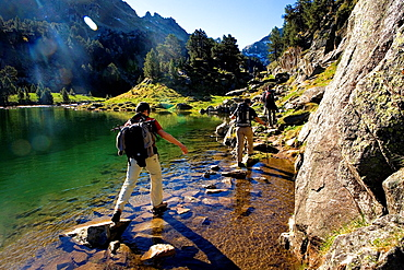 Trippers in Redon lake, Colomers cirque, Aran Valley, Aiguestortes and Estany de Sant Maurici National Park, Pyrenees, Lleida province, Catalonia, Spain