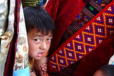 Child appearing from two women at the Thimphu festival tsechu, Bhutan