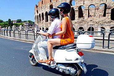 Couple riding a white vespa at the Roman Coliseum Rome Italy