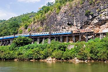 Passenger train on Krasae wooden trestle bridge Burma Railway Kanchanaburi Thailand
