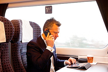 Businessman working on a tablet on a commuter train