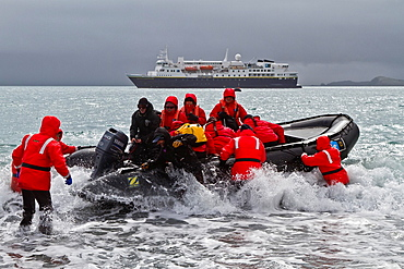 Lindblad and National Geographic Expeditions staff members conducting Zodiac landings in surf at Salisbury Plain, South Georgia Island, UK Overseas Protectorate