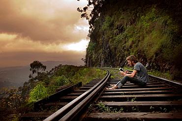 Man using tablet computer on tracks