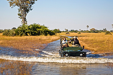 Safari vehicle driving through the Okavango Delta in Botswana, Africa