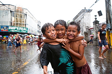 Cebu City, Philippines, 11 March 2012: Filipino kids having fun during a downpour as the raining season comes to an end
