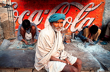 In front of a coca-cola ad, a poor tribal man is seated. He is surrounded with two men sculpting tourist souvenirs. Nathdwara, Rajasthan, India.