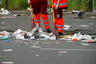 two road cleaners in litter covered street in italy