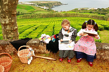 Young girls doodling on slate boards while wearing traditional garments  Porto Formoso, Sao Miguel, Azores, Portugal