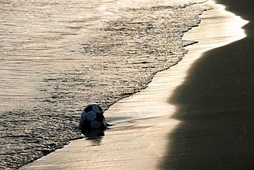one ball left on beach shore in morning sun