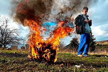 A young boy burns the used electric wires to recycle copper and sell it afterwards in the Gipsy ghetto of Chanov on outskirts of Most, Czech Republic, 22 March 2008
