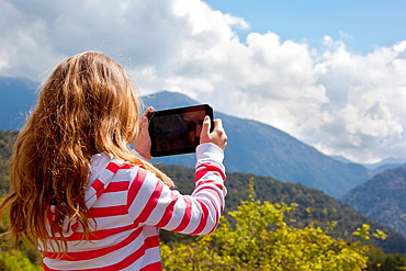 Girl using tablet computer in the mountains
