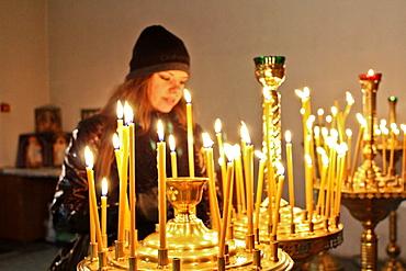 Woman lighting candles at Pechersk Lavra territory, Kiev, Ukraine