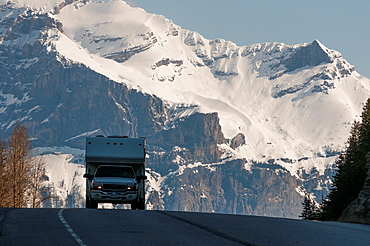 Canada, BC, Glacier National Park  Pickup truck with camper top on the crest of a hill on Highway 1 passing through the Rocky Mountains in spring