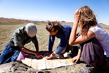 Gobi Desert, Mongolia, August 6, 2010  two girls and a man looking at a map of the Gobi desert to continue their journey