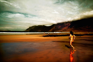 Sunset on Famara beach with girl swimmer Lanzarote