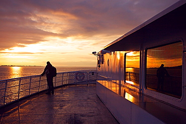 A silhouette of a man looking at the horizon on a ferry deck