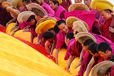 China, Gansu, Amdo, Xiahe, Monastery of Labrang Labuleng Si, Losar New Year festival, Monks furling the giant Thangka