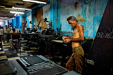 A Cuban master printer, leant against a printing machine, waits for a new load in the state print shop, Santiago de Cuba, Cuba, 4 August 2008