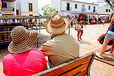Tourists resting on a bench in San Francisco Javier  Formentera, Balearic Islands, Spain