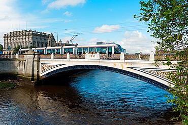 LUAS Tram on the Sean Heuston Bridge Over the River Liffey, Dublin City, Ireland