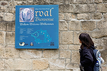 A tourist looks at the entrance sign at Orval Abbey in Villers-Devant-Orval, Belgium