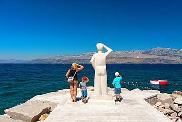 Tourists playing the statue watching the sea in Postira village on Brac island, Croatia