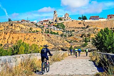 Cyclists at Toro bridge and Romanesque collegiate church of Santa Maria la Mayor, Toro, Zamora, Castille and Leon, Spain