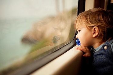 Baby with a blue dummy watching thought a window of a train