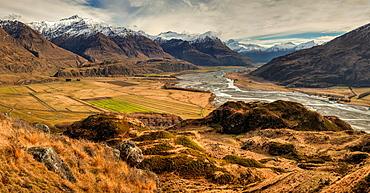Panorama from tussock grass hills above Matukituki River, Black Peak left and Mt Aspiring right, near Wanaka, Otago