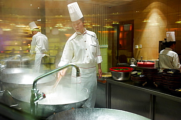 A chef preparing and cutting hand cut noodles into a vat of boiling water