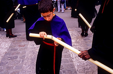 young penitent lighting the candle  Good Friday procession in Calle Carniceria  Brotherhood of `Soledad Campo Principe¥  Granada  Andalusia, Spain