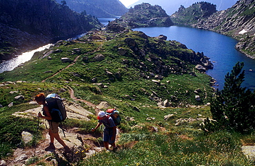 Trekking, in backgroun at right `Estany de Barbs¥Barbs lake, and at left estany de Munyidera¥Munyidera lake, Aiguestortes i Estany de Sant Maurici National Park,Pyrenees, Lleida province, Catalonia, Spain