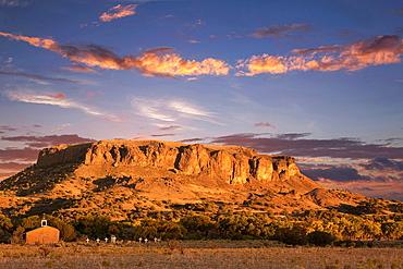 Black Mesa and Adobe church during sunset, Pajartio, New Mexico, USA
