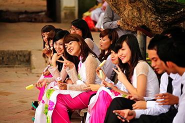 Vietnamese graduates wearing tradional dress Ao Dai at Temple of Literature, Hanoi, Vietnam