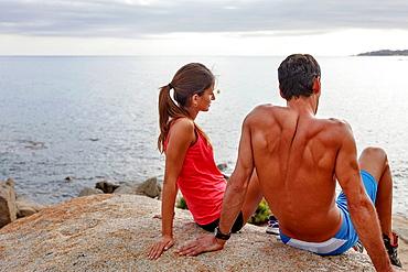 Couple on boulder overlooking ocea