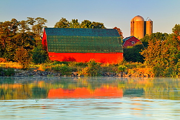 An aging red barn reflected into Gibson Lake waterway hydro controlled at dawn, Thorold, Ontario, Canada