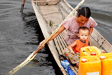 Intha women and child, cruising in her canoe through the floating houses at the Inle Lake, Shan state, Myanmar, Burma