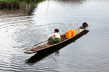 Intha women cruising in her canoe through the floating houses at the Inle Lake, Shan state, Myanmar, Burmaa