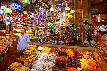 Shop worker in the Egyptian Spice Bazaar Istanbul with Turkish Delight water pipes and lamp