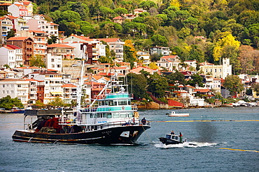 Fishermen seine fishing on the Bosphorus Strait with houses on hill at Yeni Mahalle Sariyer Turkey