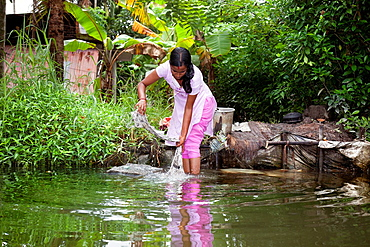 Allepey, India-September 7, 2012 An Indian woman washes her clothes on a rock in one of the canals around Alappuzha