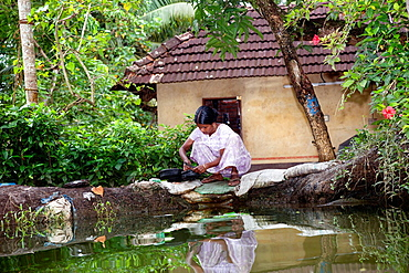 Allepy, India-September 7, 2012 Indian woman washes dishes and cutlery on the edge of one of the canals of Alappuzha