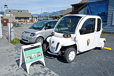 Small electric cars being charged outside Kenai Fjords National Park office and visitor center at small boat harbor, Seward, Alaska, late August