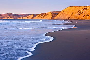 Beach, surf, and cliffs at sunrise, Drake's Beach, Point Reyes National Seashore, Marin County, California, USA