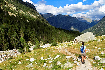 Hiker walking along Barrosa valley, a typical glacier valley of aragonese Pyrenees Huesca Spain