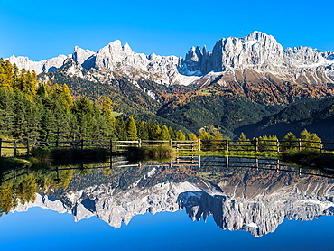 Rosengarten also called Catinaccio mountain range in the Dolomites of South Tyrol Alto Adige during autumn Reflexion of the main peaks in a pond during late afternoon The Rosengarten is part of the UNESCO world heritage site Dolomites Europe, Central Europe, Italy, South Tyrol, October