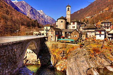 Alpine village with snow-capped mountain and a bridge over a river