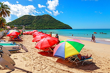 Beach and sunbeds at Rodney Bay at Gros Islet with a view to Mount Pimard, St Lucia